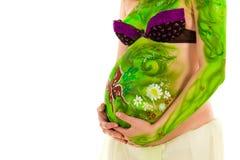 Mujer embarazada con carrocería-arte con las hojas verdes Fotos de archivo