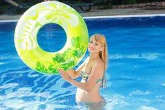 Mujer embarazada con el anillo de goma verde en la natación Imagen de archivo libre de regalías