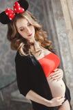 Mujer embarazada con el arqueamiento rojo Fotos de archivo