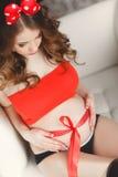 Mujer embarazada con el arqueamiento rojo Fotografía de archivo libre de regalías