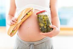 Mujer embarazada con el bocadillo y el tarro de salmueras Fotografía de archivo