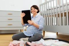 Mujer embarazada con el bolso del hospital del embalaje de la PC de la tableta imágenes de archivo libres de regalías