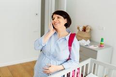 Mujer embarazada con el bolso y la llamada del hospital fotos de archivo