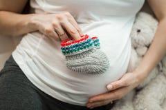 Mujer embarazada con el conejo del juguete en bedroomroom Fotografía de archivo