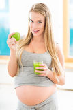 Mujer embarazada con el jugo y la manzana Imágenes de archivo libres de regalías