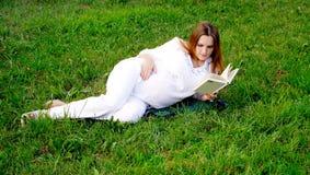 Mujer embarazada con el libro 2 Foto de archivo libre de regalías