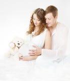Mujer embarazada con el marido que mira en el vientre imagen de archivo