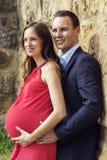 Mujer embarazada con el marido que se coloca en vertical de la pared Fotografía de archivo