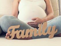 Mujer embarazada con el mensaje de la familia Fotografía de archivo