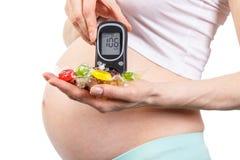 Mujer embarazada con el metro de la glucosa y caramelos coloridos, diabetes y nutrición sana durante embarazo Fotos de archivo libres de regalías