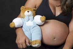 Mujer embarazada con el oso de peluche fotografía de archivo libre de regalías