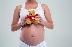 Mujer embarazada con el oso de peluche Foto de archivo libre de regalías