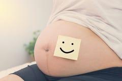 mujer embarazada con el papel de la sonrisa en el vientre Fotos de archivo libres de regalías
