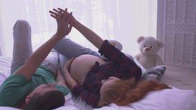 Mujer embarazada con el pelo largo y su el marido que mienten en la cama Hombre y sus manos de la toma de la esposa metrajes