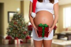 Mujer embarazada con el sombrero de santa que lleva a cabo un presente rojo debajo de su vientre imagenes de archivo