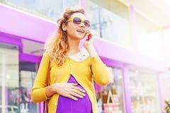 Mujer embarazada con el teléfono Fotos de archivo libres de regalías