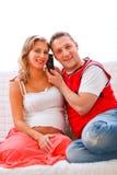 Mujer embarazada con el teléfono de discurso del marido Fotografía de archivo libre de regalías