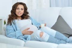 Mujer embarazada con el vidrio de leche Fotos de archivo