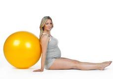 Mujer embarazada con la bola de los pilates Imagen de archivo