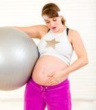 Mujer embarazada con la bola del ajuste y el vientre conmovedor Fotografía de archivo libre de regalías