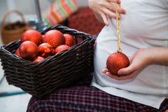 Mujer embarazada con la cesta llena de bolas rojas de la Navidad Imagenes de archivo