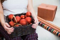 Mujer embarazada con la cesta llena de bolas rojas de la Navidad Foto de archivo libre de regalías