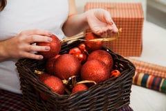 Mujer embarazada con la cesta llena de bolas rojas de la Navidad Imagen de archivo