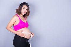 Mujer embarazada con la cinta métrica en fondo gris Foto de archivo libre de regalías