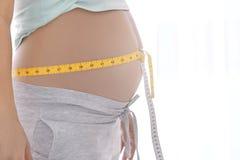 Mujer embarazada con la cinta métrica en su vientre Foto de archivo