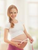 Mujer embarazada con la cinta que mide su vientre Imagen de archivo