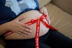 Mujer embarazada con la cinta roja Fotografía de archivo