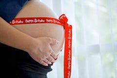 Mujer embarazada con la cinta roja Fotografía de archivo libre de regalías