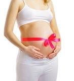 Mujer embarazada con la cinta rosada en el vientre Fotografía de archivo