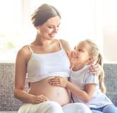 Mujer embarazada con la hija Imágenes de archivo libres de regalías