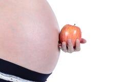 Mujer embarazada con la manzana Fotografía de archivo libre de regalías