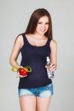 Mujer embarazada con la manzana, cinta métrica y Imagenes de archivo