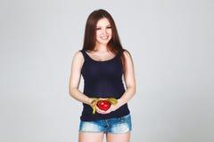 Mujer embarazada con la manzana y la cinta métrica Foto de archivo