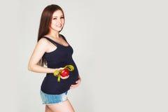 Mujer embarazada con la manzana y la cinta métrica Foto de archivo libre de regalías