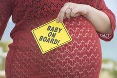 Mujer embarazada con la muestra del bebé Foto de archivo libre de regalías