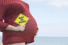 Mujer embarazada con la muestra del bebé al aire libre Foto de archivo libre de regalías