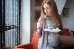 Mujer embarazada con la torta Foto de archivo