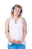 Mujer embarazada con los auriculares Fotos de archivo