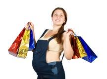 Mujer embarazada con los bolsos de compras Foto de archivo