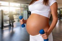 Mujer embarazada con pesas de gimnasia en su mano en un gimnasio foto de archivo libre de regalías