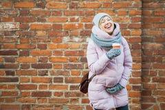 Mujer embarazada con risa del coffe en la pared de ladrillo del rojo del vintage Fotografía de archivo libre de regalías