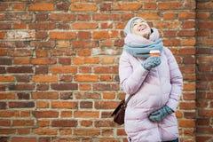 Mujer embarazada con risa del coffe en la pared de ladrillo del rojo del vintage Imagen de archivo