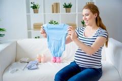 Mujer embarazada con ropa del bebé Imágenes de archivo libres de regalías