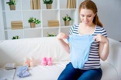 Mujer embarazada con ropa del bebé Foto de archivo libre de regalías