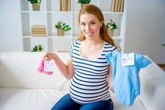 Mujer embarazada con ropa del bebé Fotos de archivo