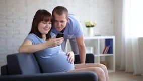 Mujer embarazada con smartphone y su marido almacen de video